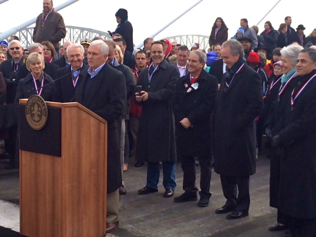 Indiana Gov Mike Pence delighted a shivering crowd by announcing that he would be the last to speak so that tens of thousands of waiting pedestrians could enjoy their one day only walk across the new vehicular bridge. (12/05/15)