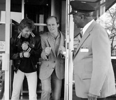 Ron Clay & Terry Meiners exiting WLRS studios in The 800 Building as doorman Sam Grandison shakes his head.  (1982)